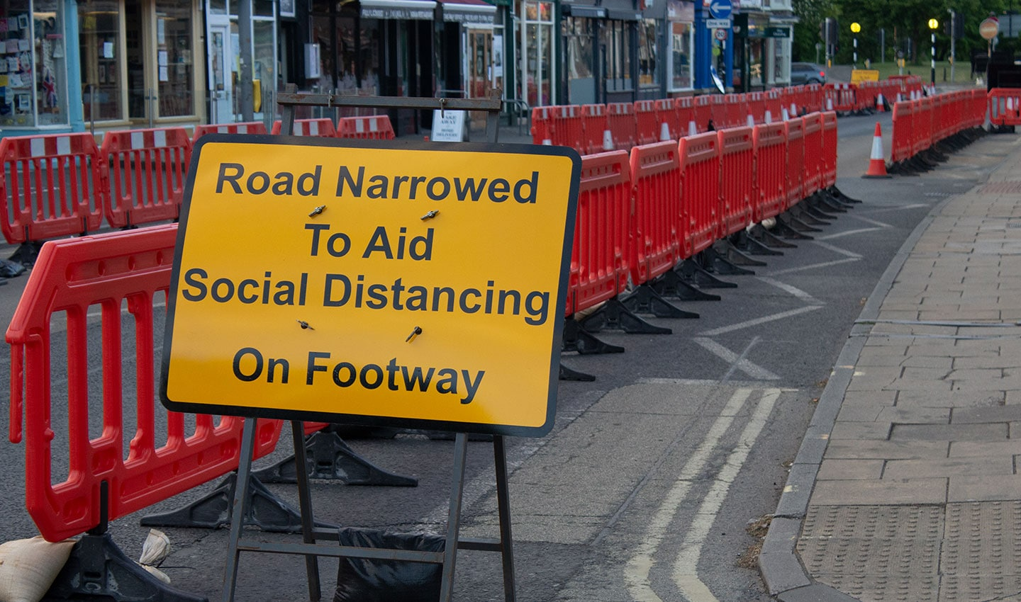 A sign in the UK informs citizens that a road is half closed to allow enough social distancing space for pedestrians.
